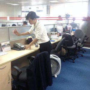 nhân viên vệ sinh công nghiệp lau vách ngăn